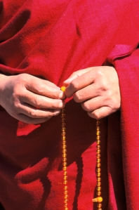 The Dalai Lama's holding mala beads in his hands.